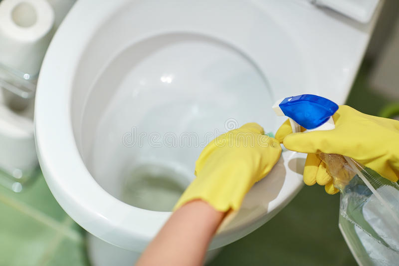 Κλείστε επάνω του χεριού με την καθαριστική καθαρίζοντας τουαλέτα στοκ εικόνα
