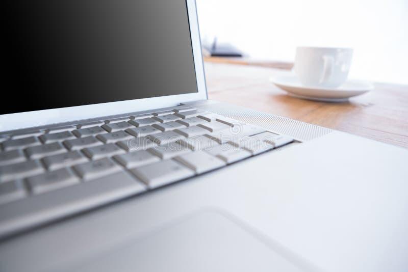 Κλείστε επάνω του lap-top και του καφέ σε ένα γραφείο στοκ εικόνα με δικαίωμα ελεύθερης χρήσης