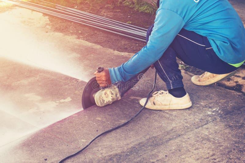 Κλείστε επάνω το άτομο χεριών που κόβει το τσιμεντένιο πάτωμα με τη μηχανή στοκ φωτογραφία με δικαίωμα ελεύθερης χρήσης