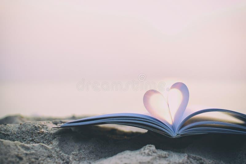 Κλείστε επάνω το βιβλίο καρδιών στην άμμο στην παραλία με το εκλεκτής ποιότητας υπόβαθρο θαμπάδων φίλτρων στοκ εικόνα με δικαίωμα ελεύθερης χρήσης