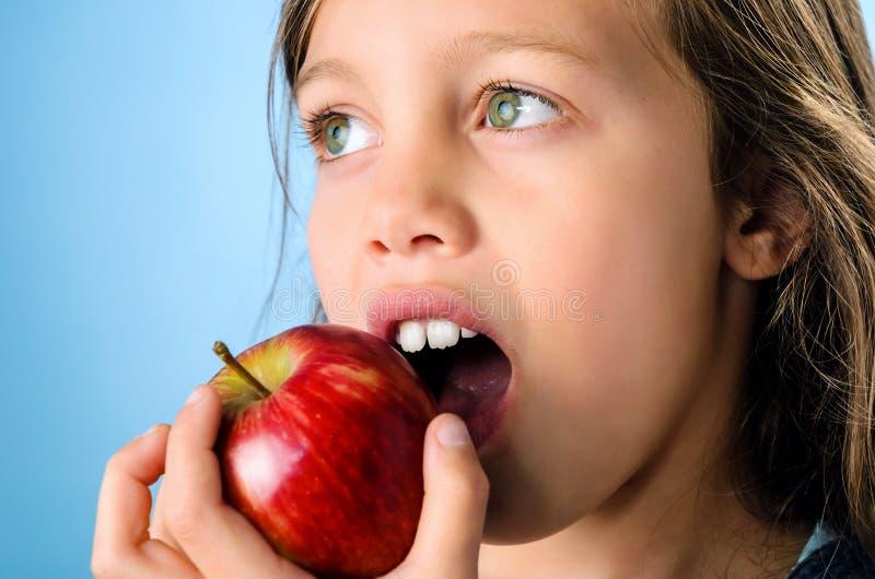 Κλείστε επάνω το πορτρέτο ενός νέου κοριτσιού που τρώει ένα μήλο στοκ εικόνες