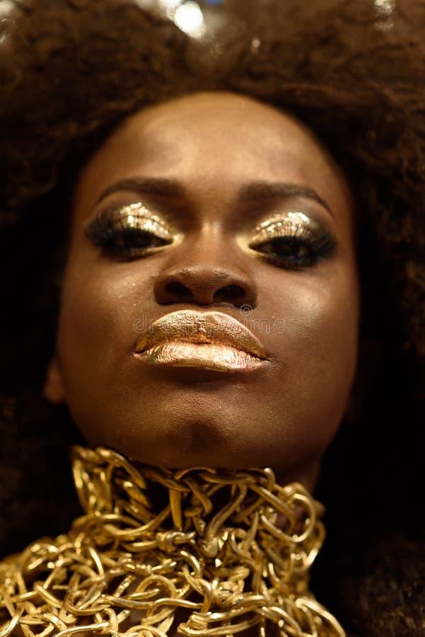 Κλείστε επάνω το πορτρέτο ομορφιάς ενός νέου θηλυκού προτύπου μόδας με τη σγουρούς τρίχα και το χρυσό makeup στοκ εικόνα με δικαίωμα ελεύθερης χρήσης