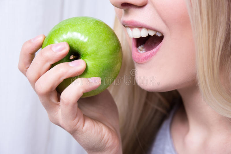 Κλείστε επάνω το πορτρέτο της γυναίκας δαγκώνοντας το πράσινο μήλο στοκ φωτογραφίες