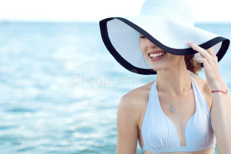Κλείστε επάνω το πορτρέτο της πανέμορφης χαμογελώντας κυρίας glam που κρύβει το μισό του προσώπου της πίσω από το ευρύ καπέλο χεί στοκ εικόνες