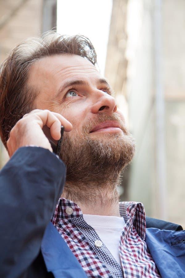 Κλείστε επάνω το πορτρέτο του χαμογελώντας ατόμου που μιλά σε ένα κινητό τηλέφωνο στοκ εικόνα