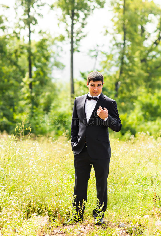 Κλείστε επάνω το πορτρέτο του όμορφου μοντέρνου νεόνυμφου στο μαύρο κλασικό κοστούμι υπαίθρια στοκ εικόνες