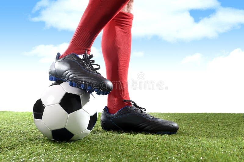 Κλείστε επάνω το ποδοσφαιριστή ποδιών ποδιών στις κόκκινες κάλτσες και τα μαύρα παπούτσια που παίζει με τη σφαίρα στην πίσσα χλόη στοκ φωτογραφίες