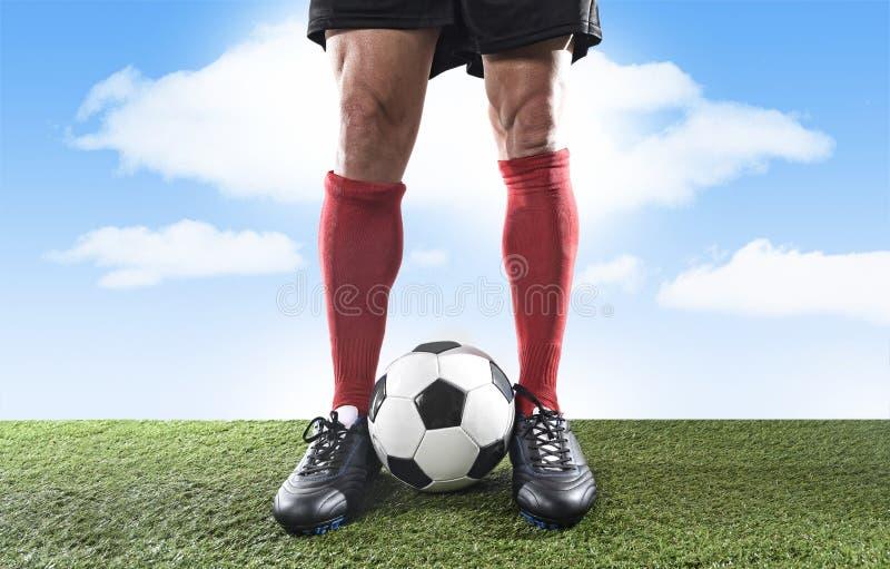 Κλείστε επάνω το ποδοσφαιριστή ποδιών ποδιών στις κόκκινες κάλτσες και τα μαύρα παπούτσια που παίζει με τη σφαίρα στην πίσσα χλόη στοκ εικόνες