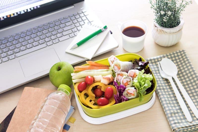 Κλείστε επάνω το πράσινο καλαθάκι με φαγητό στο χώρο εργασίας του λειτουργώντας γραφείου, θεραπεύστε στοκ εικόνες
