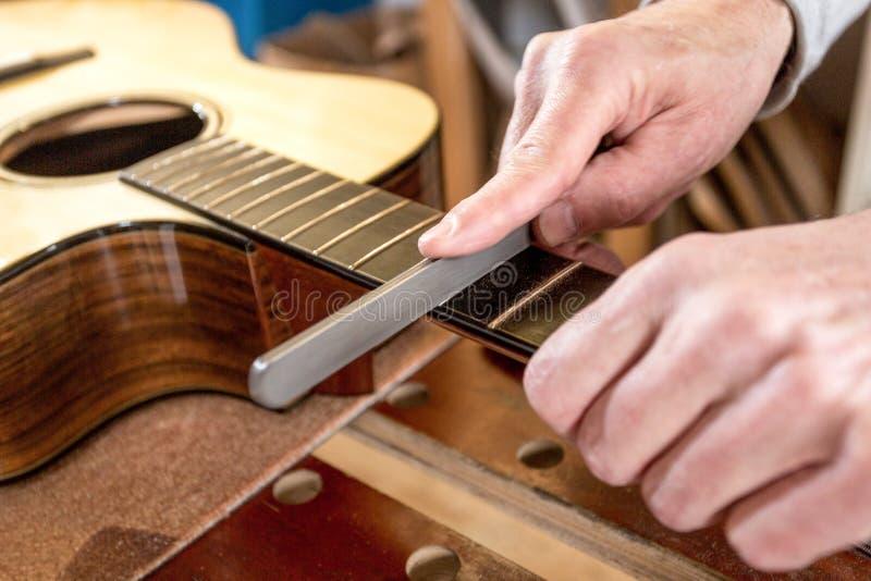 Κλείστε επάνω το των χεριών βιοτεχνών ` s, αρχειοθετώντας τους μαιάνδρους μιας κιθάρας στοκ εικόνες
