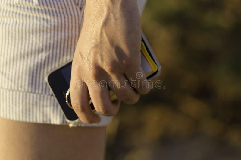 Κλείστε επάνω το χέρι κρατώντας ένα τηλέφωνο στοκ εικόνες
