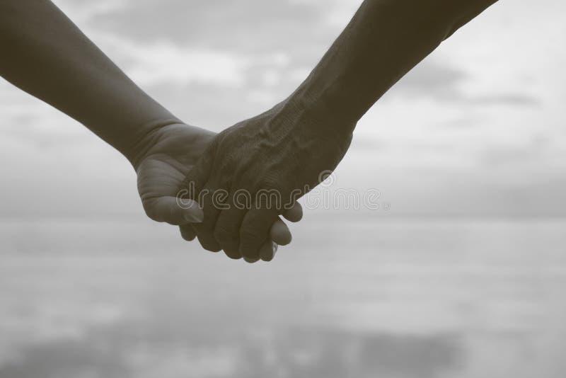 Κλείστε επάνω το χέρι του ανώτερου χεριού εκμετάλλευσης ζευγών μαζί κοντά στην παραλία στην παραλία, γραπτό χρώμα εικόνων, φιλτρα στοκ φωτογραφία με δικαίωμα ελεύθερης χρήσης