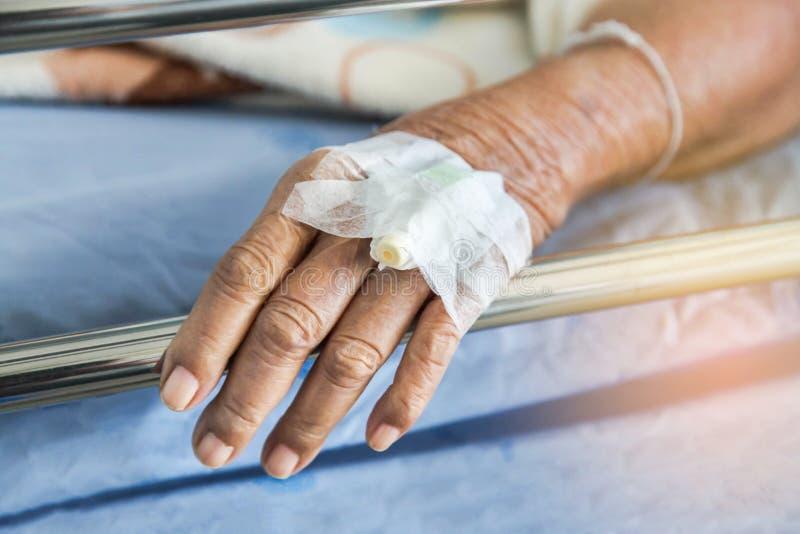 Κλείστε επάνω το χέρι του ηλικιωμένου ασθενή με τον ενδοφλέβιο καθετήρα για το βούλωμα εγχύσεων υπό εξέταση στοκ φωτογραφία με δικαίωμα ελεύθερης χρήσης