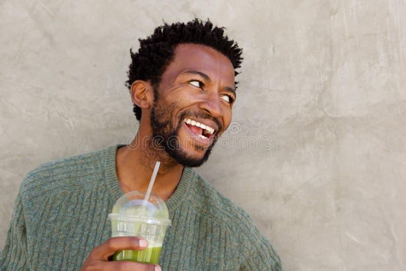 Κλείστε επάνω το όμορφο άτομο αφροαμερικάνων που κρατά το υγιές ποτό στοκ φωτογραφία