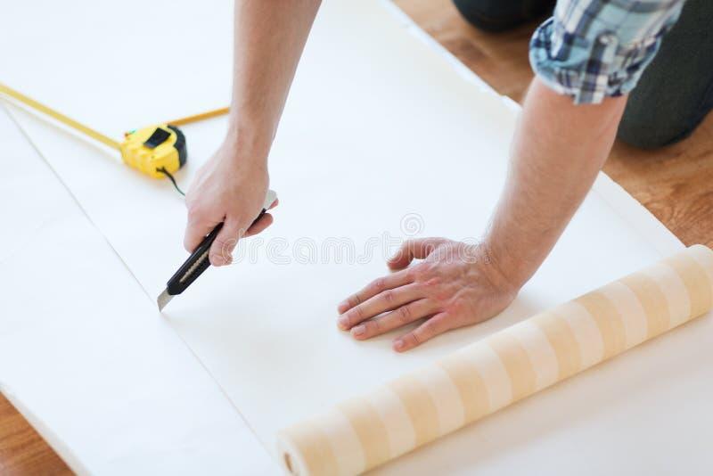 Κλείστε επάνω των αρσενικών χεριών κόβοντας την ταπετσαρία στοκ εικόνα με δικαίωμα ελεύθερης χρήσης