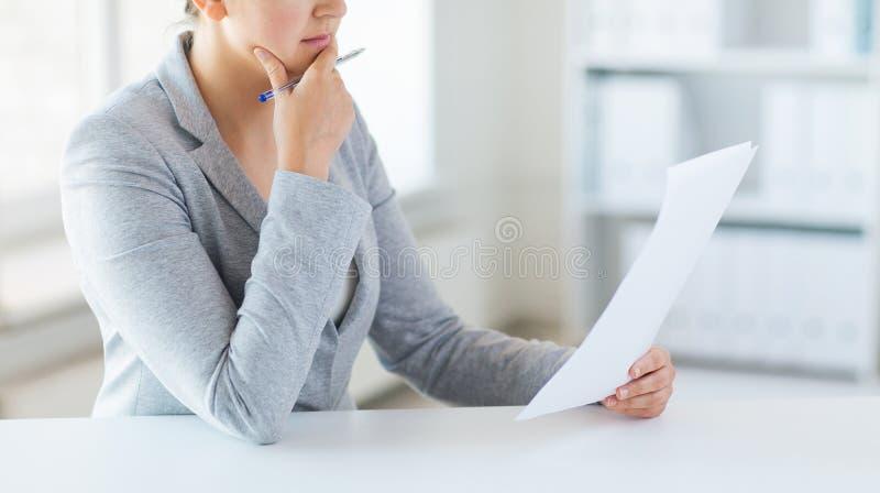 Κλείστε επάνω των εγγράφων ανάγνωσης γυναικών ή της φορολογικής έκθεσης στοκ φωτογραφία με δικαίωμα ελεύθερης χρήσης