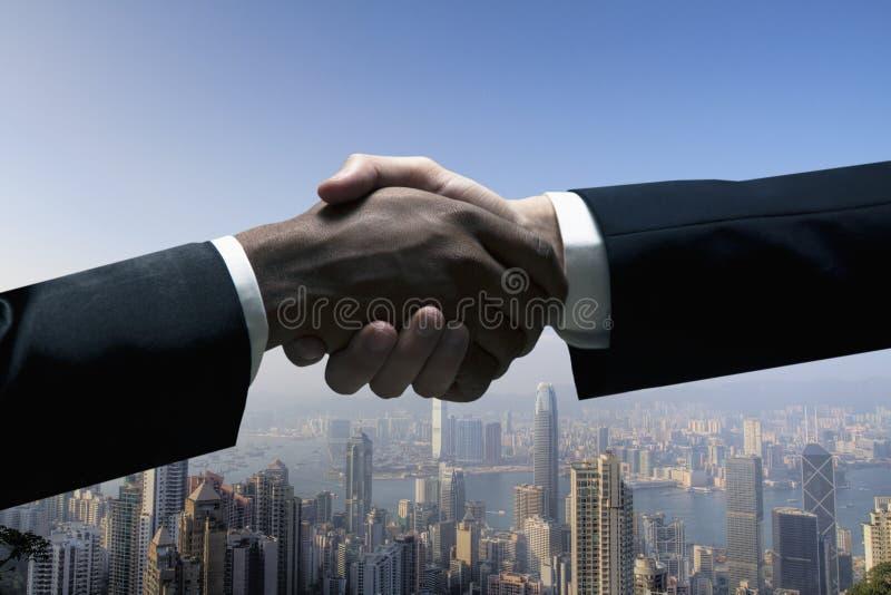 Κλείστε επάνω των επιχειρηματιών που τινάζουν τα χέρια με τη εικονική παράσταση πόλης στο υπόβαθρο στοκ φωτογραφία με δικαίωμα ελεύθερης χρήσης
