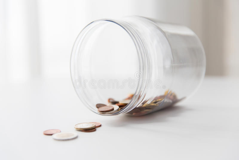 Κλείστε επάνω των ευρο- νομισμάτων στο βάζο γυαλιού στον πίνακα στοκ φωτογραφία