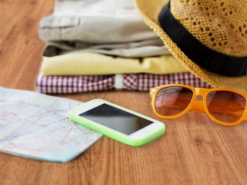 Κλείστε επάνω των θερινών ενδυμάτων και του χάρτη ταξιδιού στο πάτωμα στοκ φωτογραφία με δικαίωμα ελεύθερης χρήσης