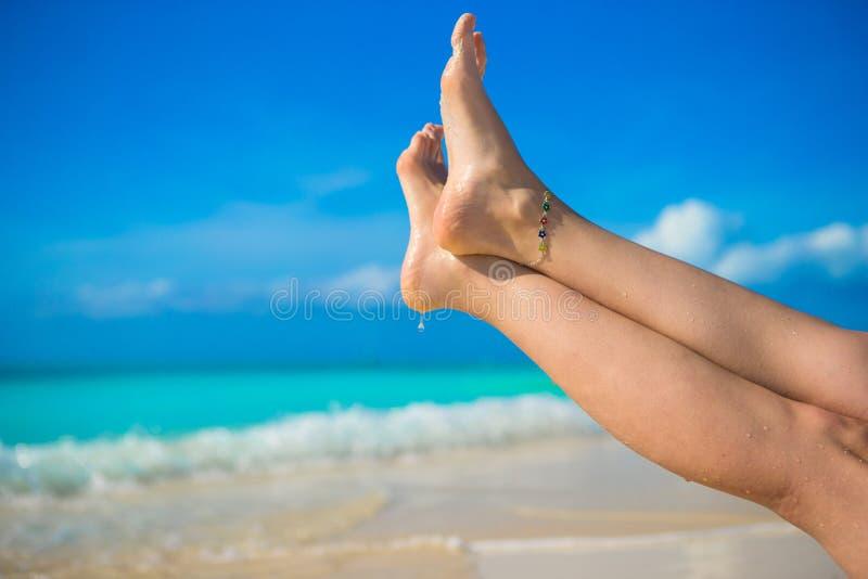 Κλείστε επάνω των θηλυκών ποδιών στην άσπρη αμμώδη παραλία στοκ εικόνες
