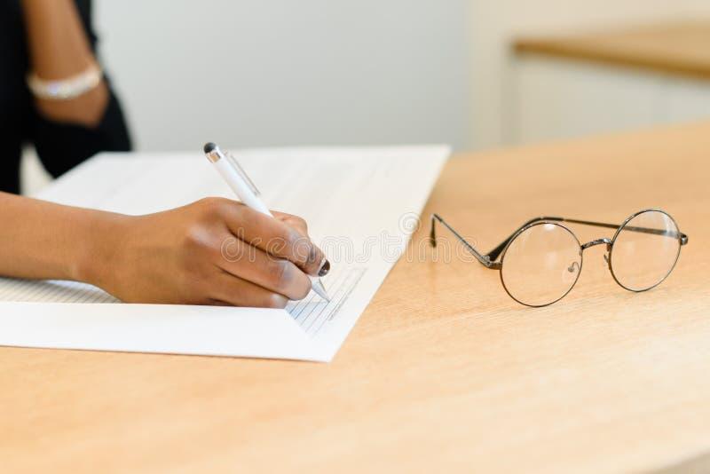 Κλείστε επάνω των θηλυκών χεριών γράφοντας στο σημειωματάριο στο ξύλινο γραφείο με eyeglasses στοκ εικόνες