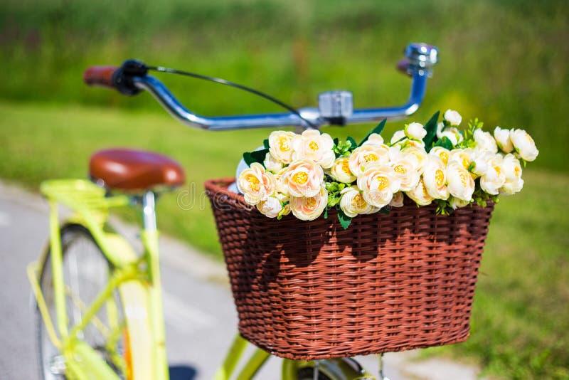 Κλείστε επάνω των λουλουδιών στο ψάθινο καλάθι του εκλεκτής ποιότητας ποδηλάτου στοκ φωτογραφίες