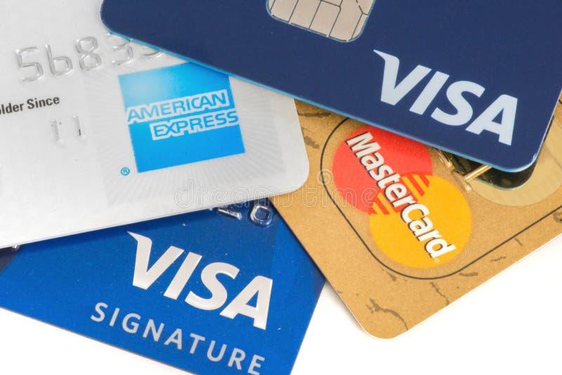 Κλείστε επάνω των πιστωτικών καρτών με MasterCard, τη Visa και τα λογότυπα της American Express στο άσπρο υπόβαθρο, επεξηγηματικό στοκ εικόνα
