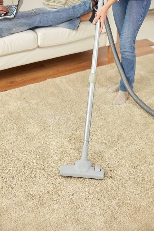 Κλείστε επάνω των ποδιών ζευγών και της ηλεκτρικής σκούπας στο σπίτι στοκ εικόνα με δικαίωμα ελεύθερης χρήσης