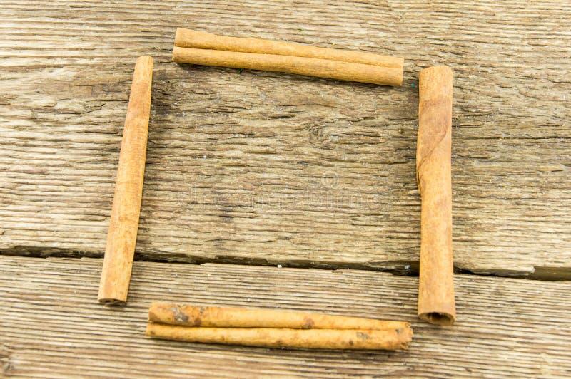 Κλείστε επάνω των ραβδιών κανέλας στο αγροτικό ξύλο στοκ φωτογραφίες