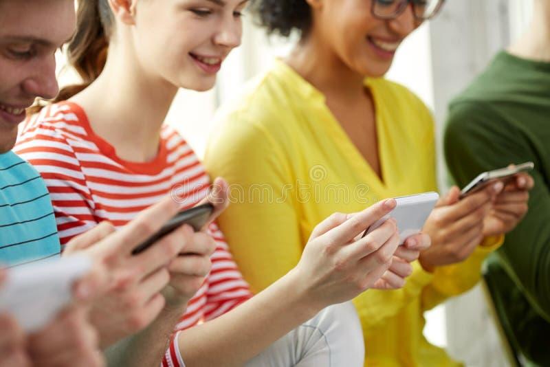 Κλείστε επάνω των σπουδαστών με τα smartphones στο σχολείο στοκ εικόνα με δικαίωμα ελεύθερης χρήσης
