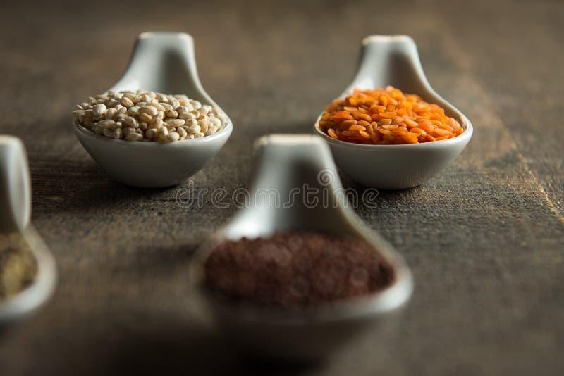 Κλείστε επάνω των φακών και quinoa στα άσπρα κουτάλια στο ξύλο στοκ εικόνα