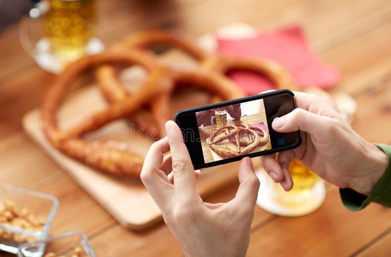Κλείστε επάνω των χεριών απεικονίζοντας pretzel από το smartphone στοκ φωτογραφίες με δικαίωμα ελεύθερης χρήσης