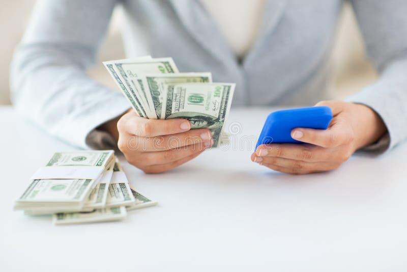 Κλείστε επάνω των χεριών γυναικών με το smartphone και τα χρήματα στοκ εικόνα
