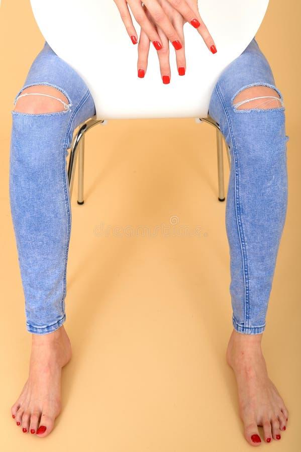 Κλείστε επάνω των χεριών και των ποδιών μιας πρότυπης συνεδρίασης στα σχισμένα τζιν στοκ φωτογραφία με δικαίωμα ελεύθερης χρήσης