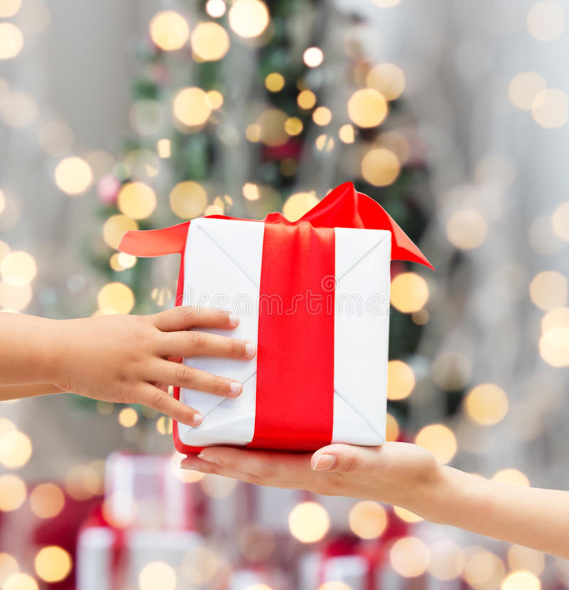 Κλείστε επάνω των χεριών παιδιών και μητέρων με το κιβώτιο δώρων στοκ εικόνες
