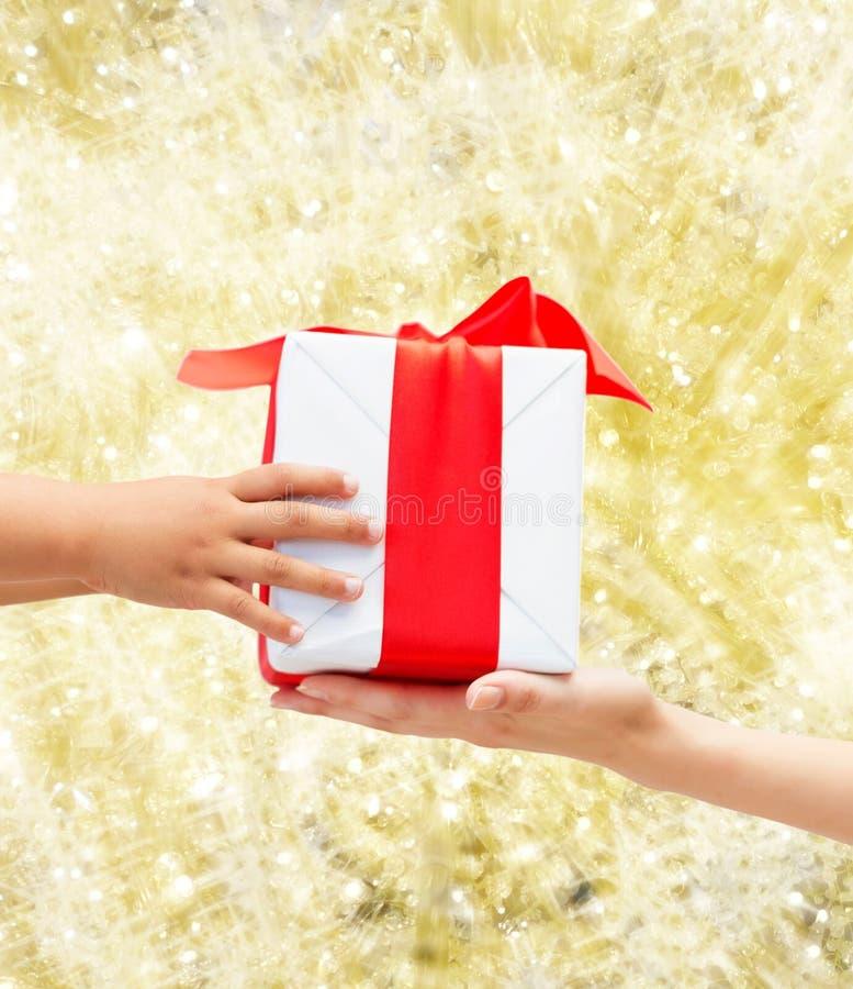 Κλείστε επάνω των χεριών παιδιών και μητέρων με το κιβώτιο δώρων στοκ φωτογραφία