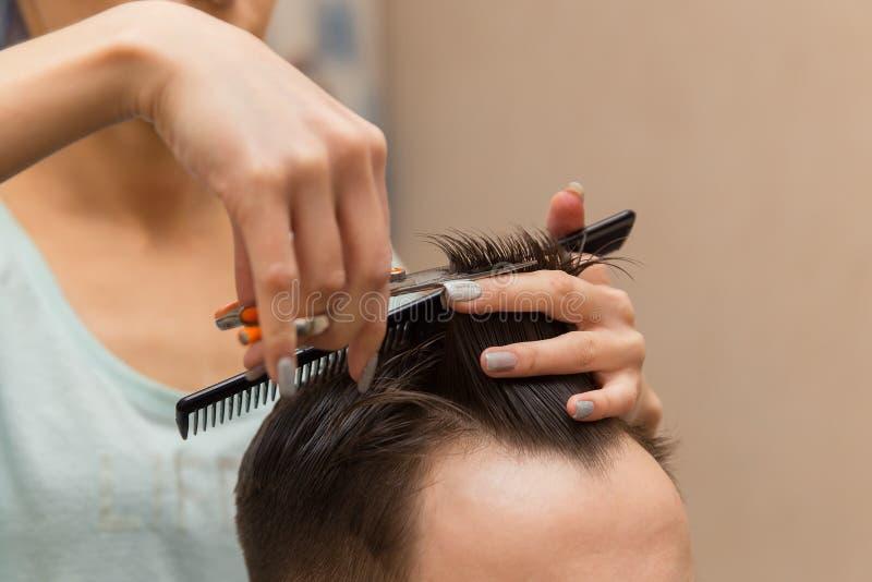 Κλείστε επάνω των χεριών του νέου κουρέα που κάνει το κούρεμα στο ελκυστικό άτομο στο barbershop στοκ φωτογραφία με δικαίωμα ελεύθερης χρήσης
