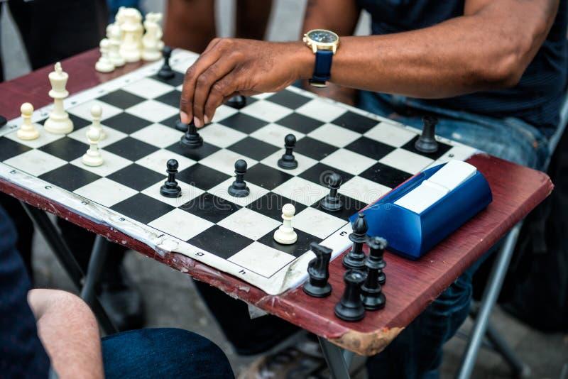 Κλείστε επάνω των χεριών των ανθρώπων που παίζουν το γρήγορο σκάκι στην οδό με το χρονόμετρο στοκ φωτογραφία