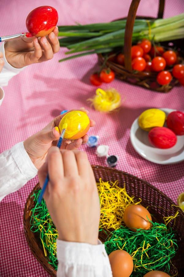 Κλείστε επάνω των χρωματίζοντας αυγών μικρών κοριτσιών και μητέρων για Πάσχα στοκ φωτογραφία με δικαίωμα ελεύθερης χρήσης