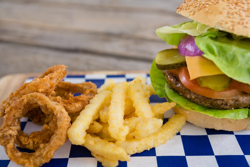 Κλείστε επάνω burger και κρεμμυδιών των δαχτυλιδιών με τις τηγανιτές πατάτες στοκ εικόνες με δικαίωμα ελεύθερης χρήσης
