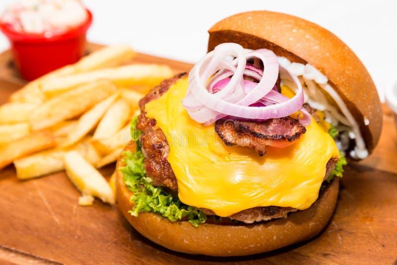 Κλείστε επάνω burger χοιρινού κρέατος με το τυρί, φυτικός και εξυπηρετημένος με τα τηγανητά στοκ εικόνες