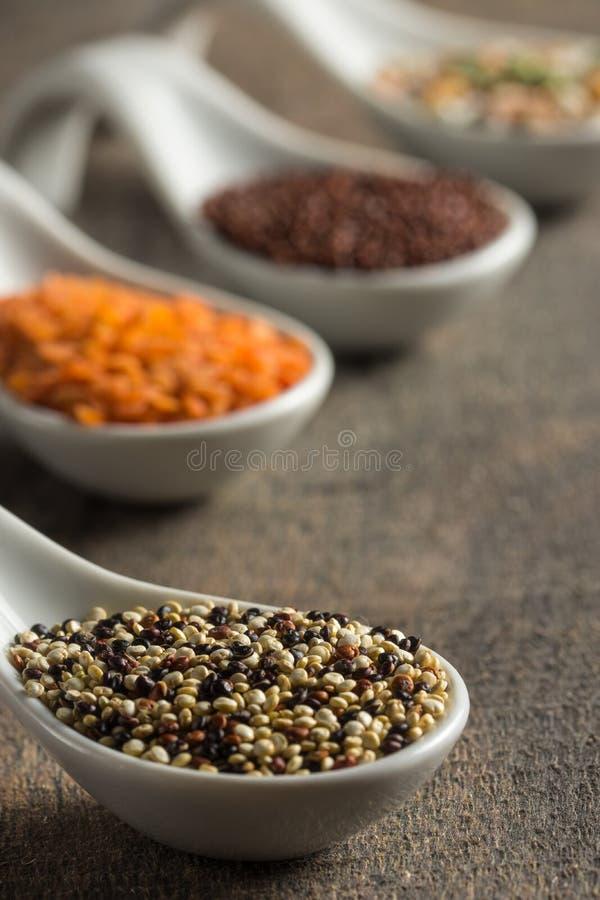 Κλείστε επάνω quinoa στα άσπρα κουτάλια στο ξύλο στοκ φωτογραφία