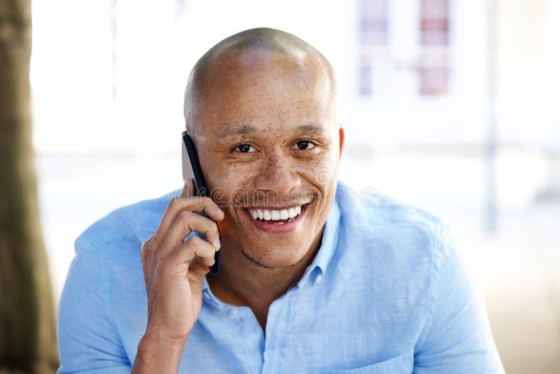 Κλείστε ομιλία επιχειρηματιών επάνω χαμόγελου την αφρικανική στο κινητό τηλέφωνο στοκ εικόνα