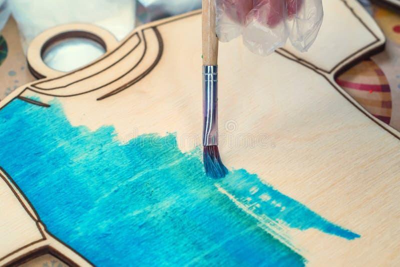 Κλείστε τον επάνω χρωματίζοντας ξύλινο πίνακα στη μορφή της μπλούζας στοκ φωτογραφία