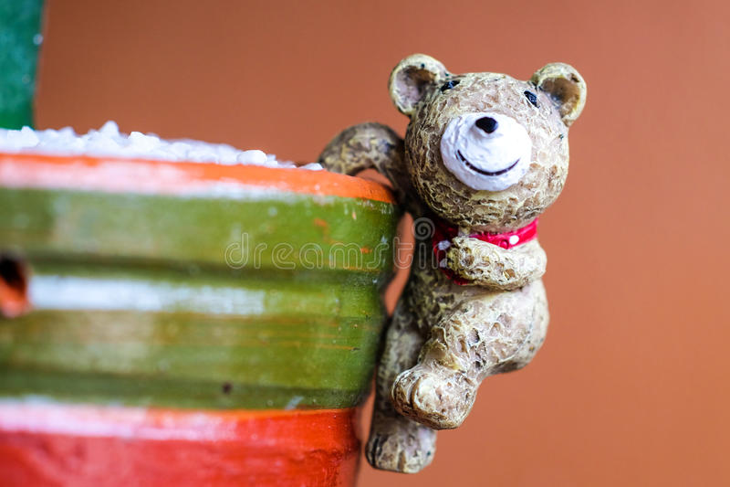 Κλειστή επάνω εικόνα της κεραμικής αρκούδας στο ζωηρόχρωμο δοχείο cacus με το Οράν στοκ φωτογραφία
