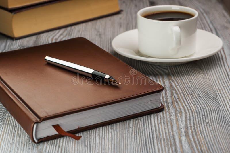 Κλειστό σημειωματάριο με τη μάνδρα πηγών στον αγροτικό πίνακα Πέννα στο σημειωματάριο στοκ φωτογραφίες με δικαίωμα ελεύθερης χρήσης