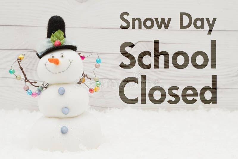 Κλειστό σχολείο μήνυμα με έναν χιονάνθρωπο στοκ εικόνες