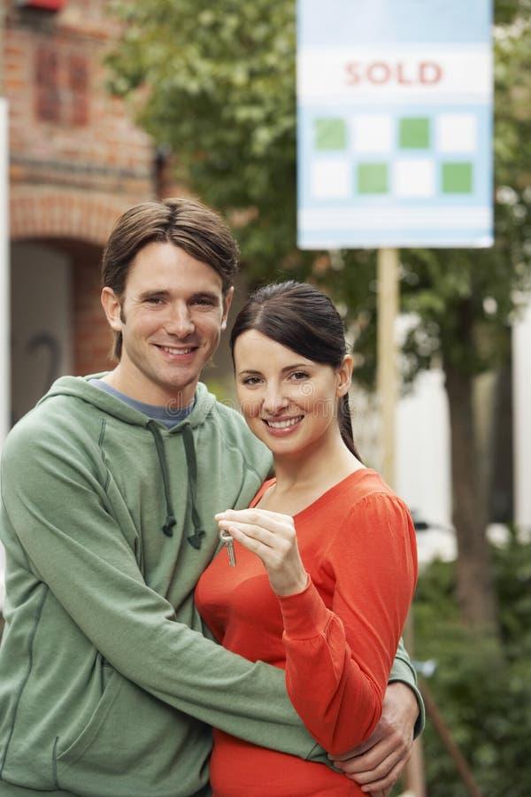 Κλειδί εκμετάλλευσης ζεύγους μπροστά από το νέο σπίτι με το πωλημένο σημάδι στοκ φωτογραφία με δικαίωμα ελεύθερης χρήσης