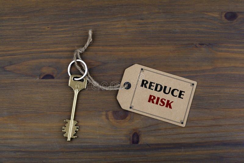 Κλειδί και μια σημείωση για έναν ξύλινο πίνακα με το κείμενο - ΜΕΙΩΣΤΕ τον ΚΙΝΔΥΝΟ στοκ εικόνες με δικαίωμα ελεύθερης χρήσης