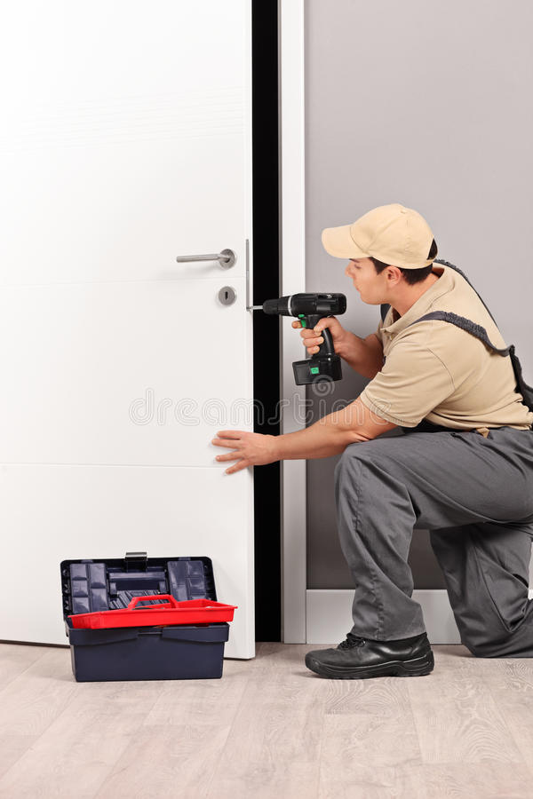 Κλειδαράς που εγκαθιστά μια κλειδαριά πορτών στοκ φωτογραφία με δικαίωμα ελεύθερης χρήσης